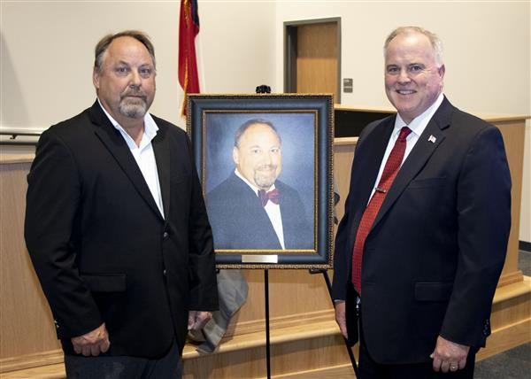 Mr. Rick Stout takes a photo with Dr. Barry Collins as his portrait is revealed