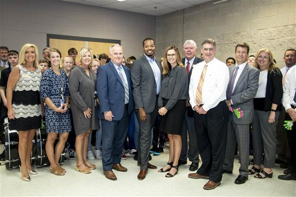 Daniel Scott takes a photo with district staff, Board members, the SBMS band and others that surprised him with the news