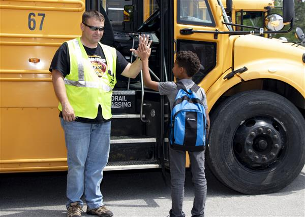 An OCS bus driver gives a student a high five
