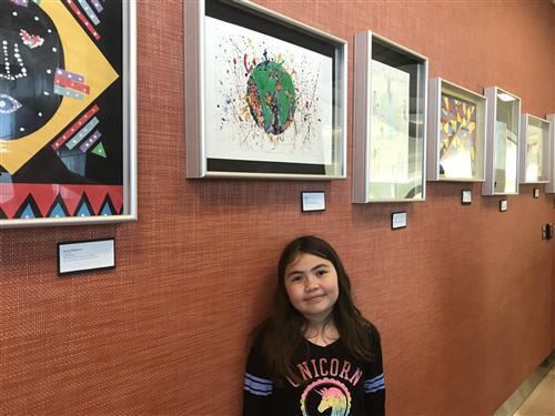 Fourth grader Angelica Lakes poses with her artwork