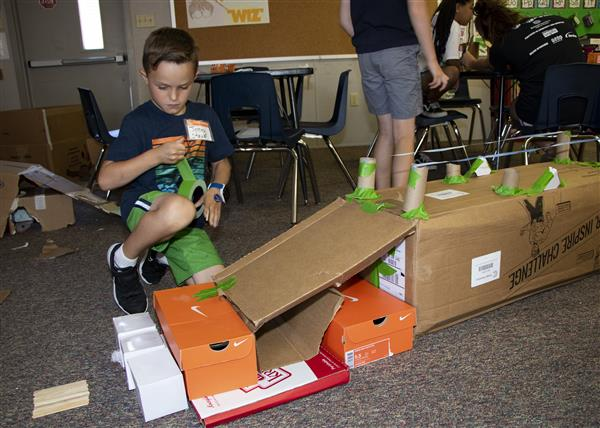 A camper builds a structure for his robot to navigate