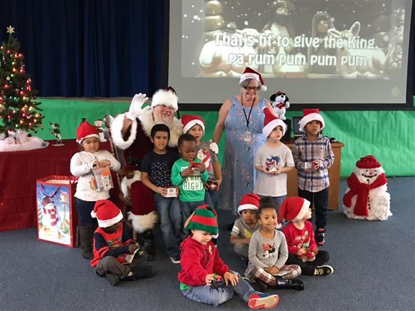 Santa takes a photo with students at Thompson Early Childhood Center