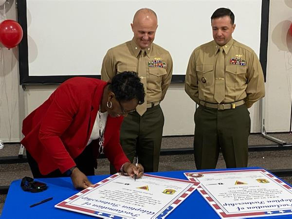 JCE Principal Deborah Hoffman signs the adoption proclamations with officers from MAG-29 and HMHT-302