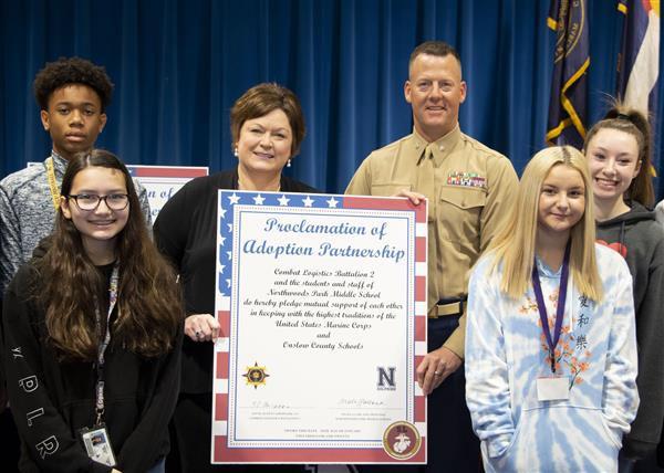 Principal Angela Garland, LtCol Scott Clippinger and NWPMS students at the adoption ceremony