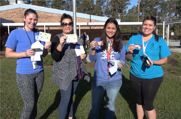 Teachers from Swansboro Elementary School smile and pose with gift cards they received