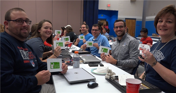 Teachers from Swansboro High School hold up their gift cards they received from their community