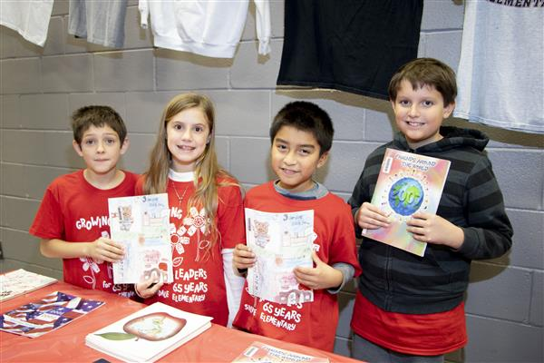 Silverdale Elementary students show some of the school's yearbooks from years past
