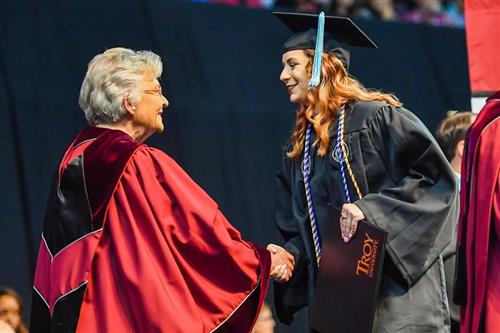 Mrs. Saenz at her college graduation, shaking hands with governor Kay Ivy