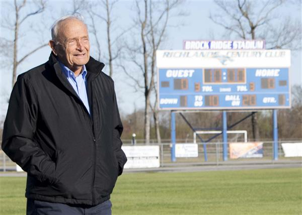 Mr. Brock Ridge stands in front of the scoreboard at the RHS stadium, which was recently named in his honor