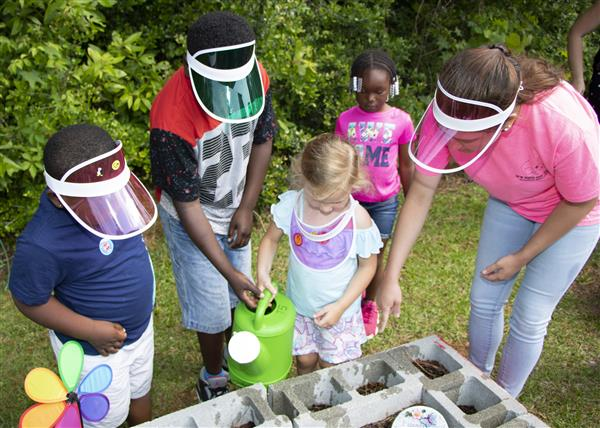 Students water plants at OCLC's Classroom Without Walls