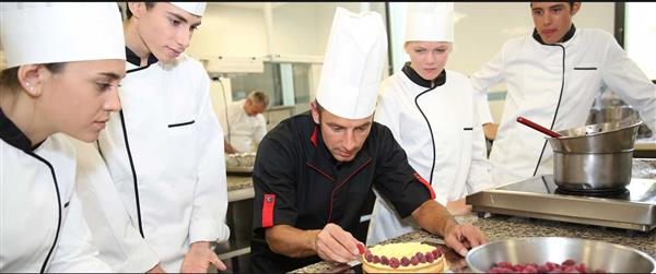 Future chefs observing Culinary arts instructor