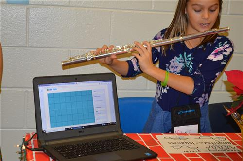 A student plays the flute to show how to graph sound waves on the computer